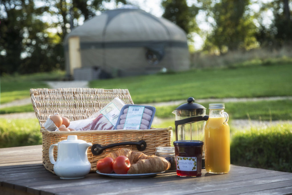 Breakfast hamper with sausages, bacon, eggs and drinks on table in front of yurt