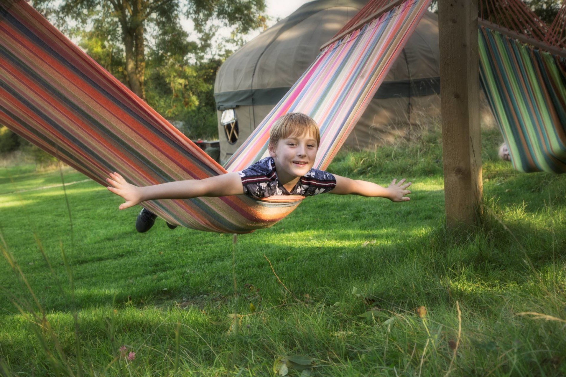 Young boy on a hammock outside the yurt