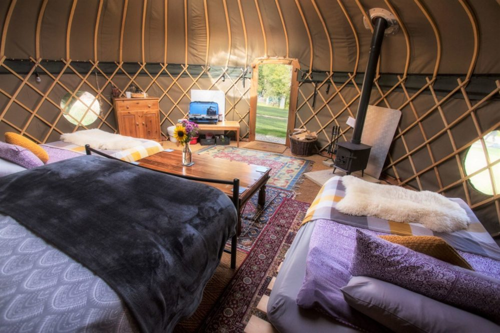 Inside one of the yurts with a king size bed, double futons and woodburner