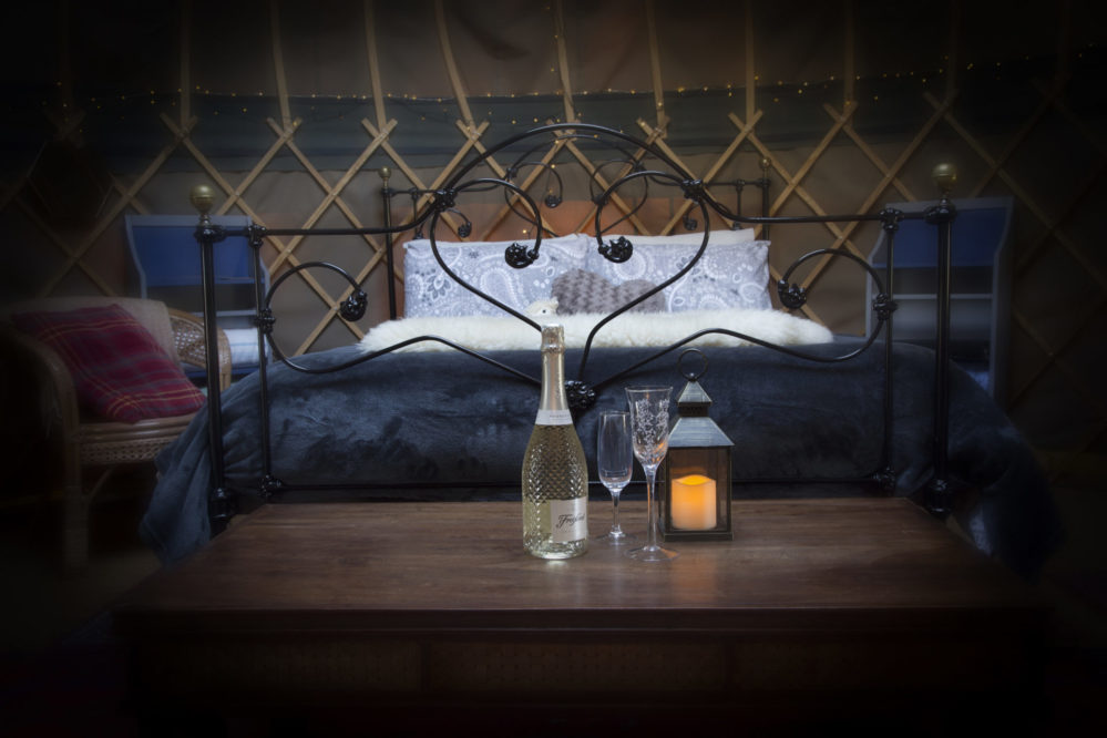 Romantic scene with bed and bottle of fizz