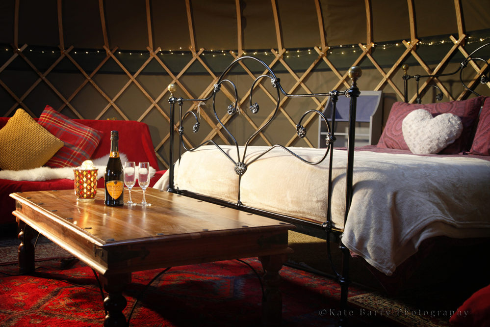 Buttercup yurt's king size bed and a bottle of fizz