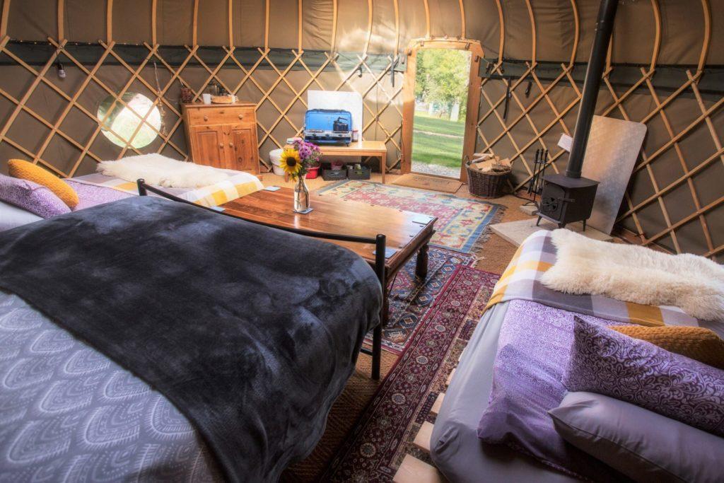 Daisy at Campden Yurts, Internal shot with beds, futons and woodburner